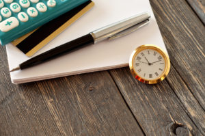 Pocket Watch Next to Pen, Paper and Calculator
