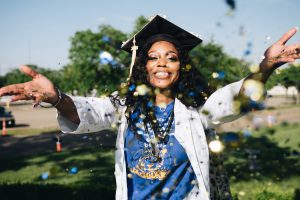 woman throwing confetti in celebration of graduating